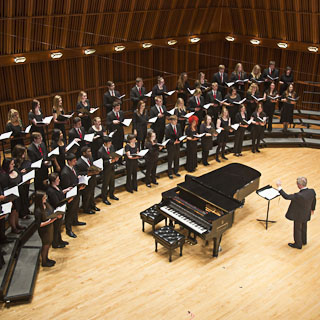 A mixed chorus of male and female singers on stage with a piano and conductor in front